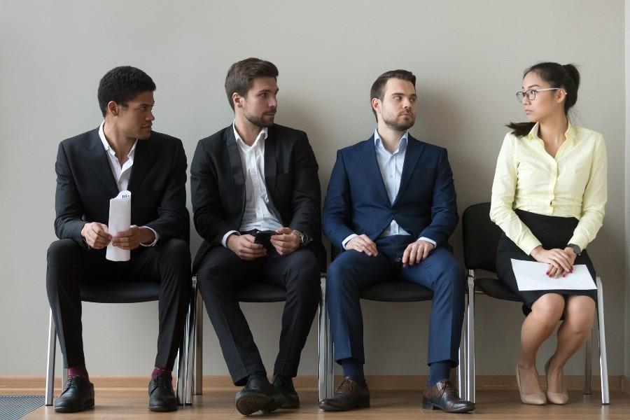 Uomini in attesa di colloquio guardano con sospetto una donna anche lei in attesa di colloquio lavorativo.