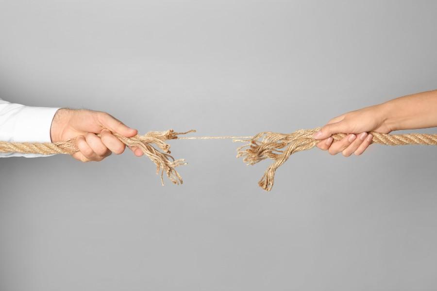 strategie di gestione dei conflitti: nell'immagine mani che tirano una corda che si sta spezzando