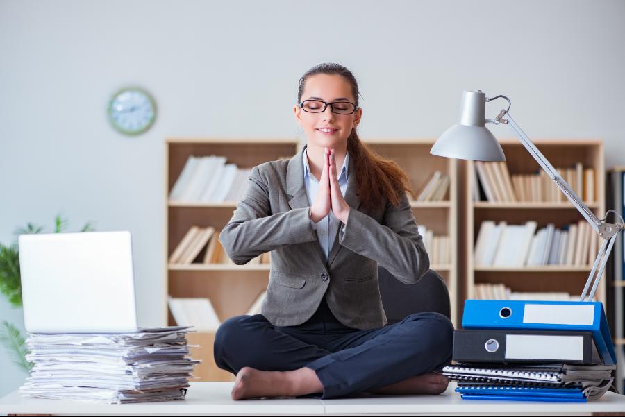 strategie di gestione dei conflitti: nell'immagine una ragazza fa yoga alla scrivania