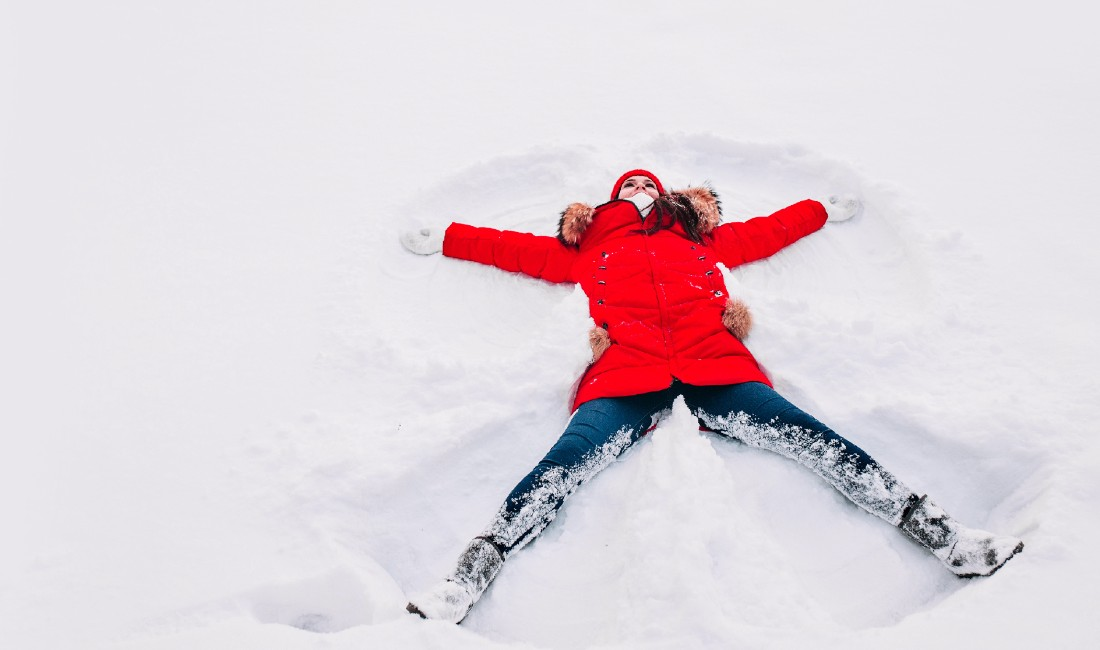 Prepararsi ad affrontare l'inverno: nell'immagine una ragazza crea un angelo di neve.