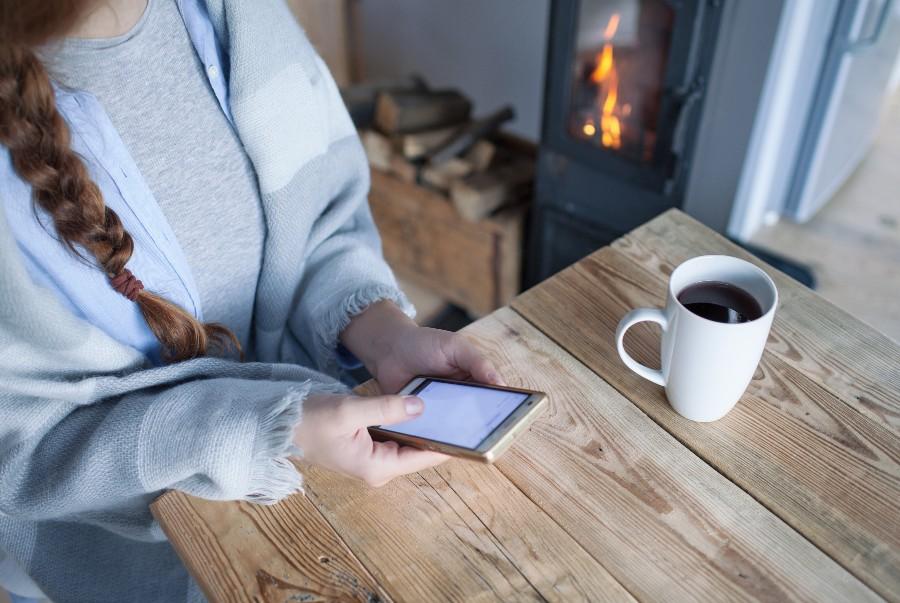 Prepararsi ad affrontare l'inverno: nell'immagine una ragazza guarda lo smartphone, sullo sfondo il camino acceso.