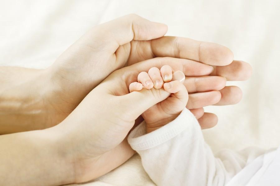 Non volere figli: nell'immagine mani di mamma, papà, bambino.