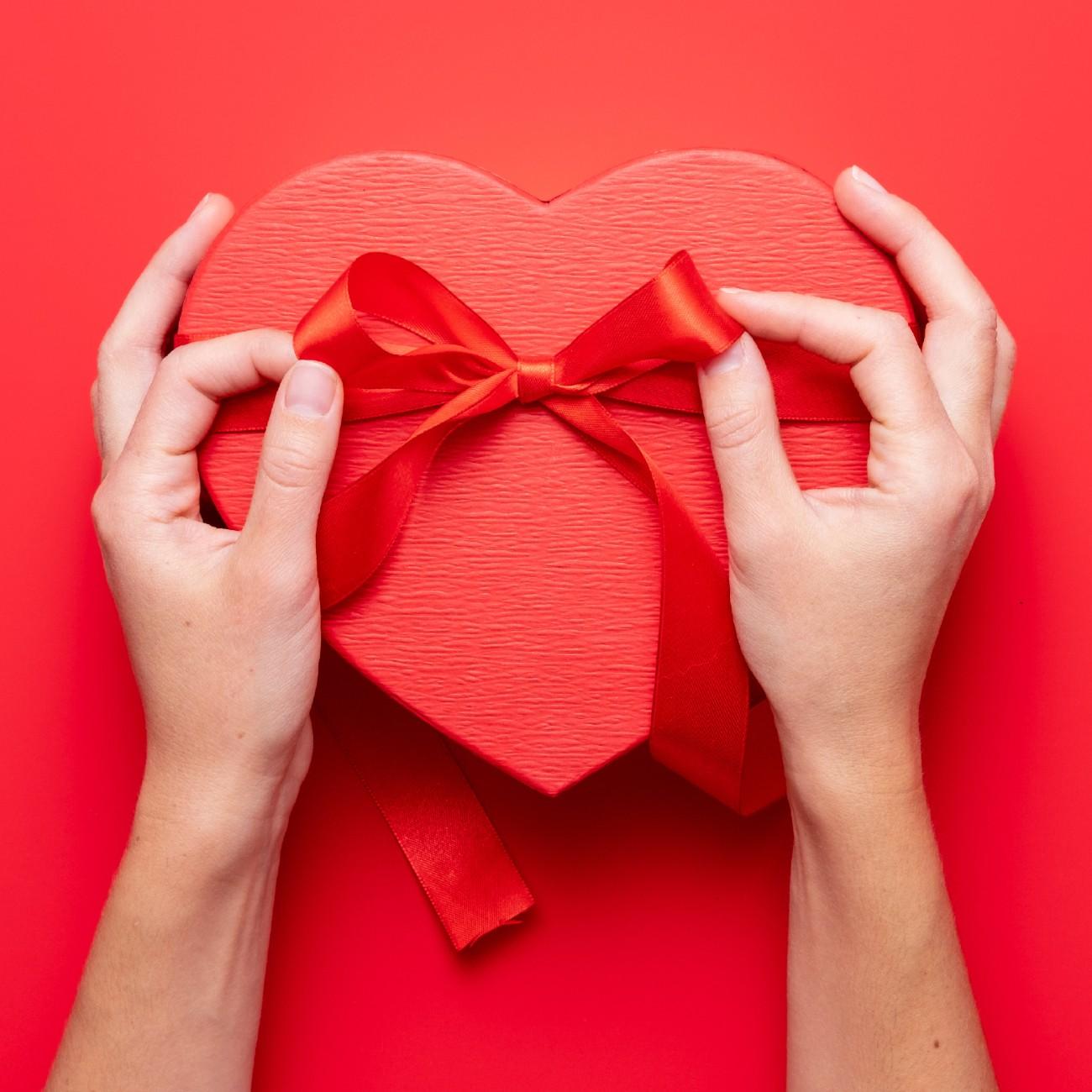 Regali di coppia per San Valentino: mani femminili confezionano un pacchetto a forma di cuore