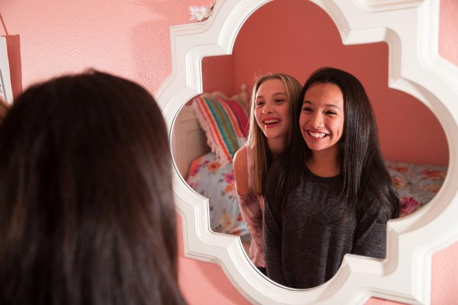 Due ragazze adolescenti e sorridenti allo specchio